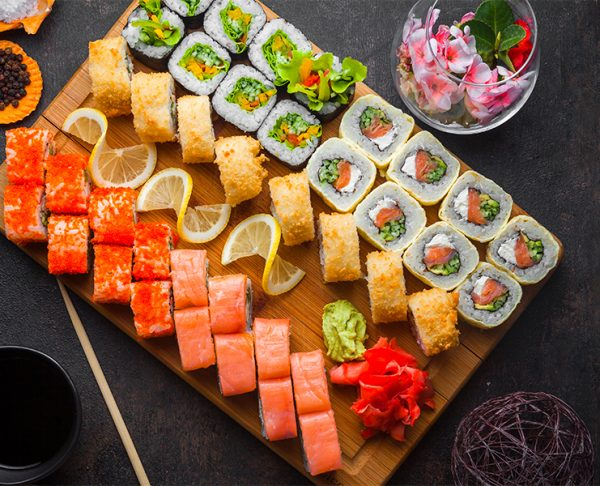 Top view sushi set with soy sauce and chopsticks in wooden servi